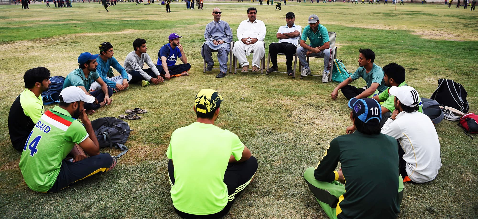 Asghar Khan head coach of the ICMS cricket club and former coach of players in the Afghan national cricket team, discusses cricket with young Pakistani cricketers at the Gymkhana Cricket Academy in Peshawar. — AFP