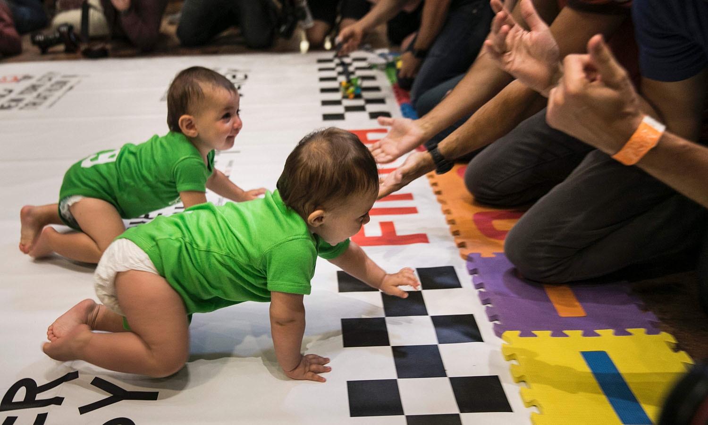 دودھ کی بوتل اور کھلونوں کو دیکھ کر بچے اپنے والدین کی جانب تیزی سے دوڑے — فوٹو/ اے ایف پی