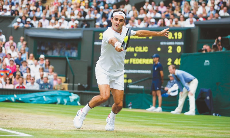 LONDON: Switzerland's Roger Federer hits a return to Marin Cilic of Croatia during the Wimbledon final at the All England Lawn Tennis Club on Sunday.—AFP
