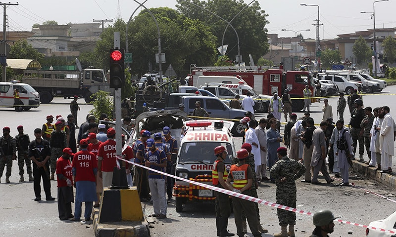 Security officers and volunteers inspect the site of a bombing in Peshawar. —AP