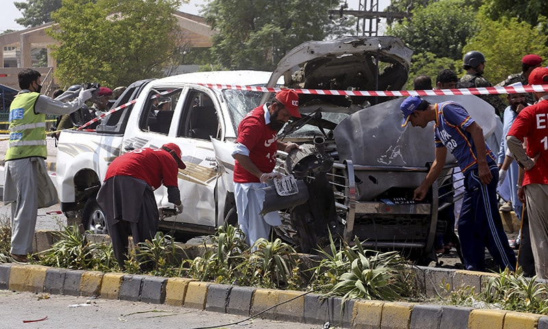 Security officers and volunteers collect evidence at the site of the bombing in Peshawar.— AP