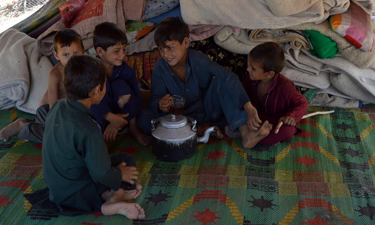 Children sit around a pot of tea inside a makeshift house | Photo by Musharraf Ali
