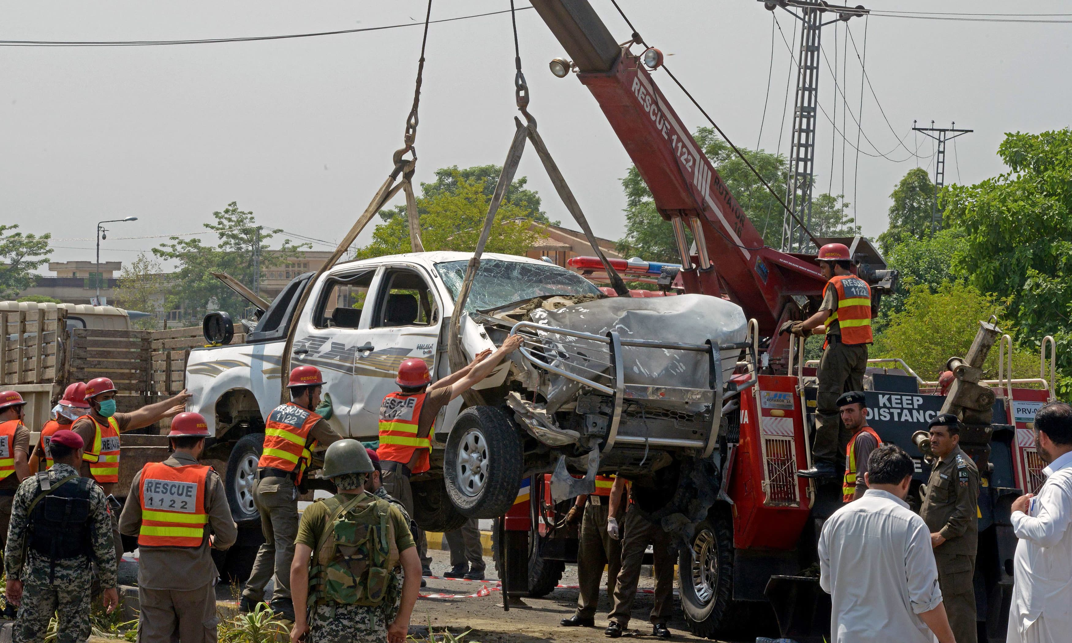 Officials lift a security vehicle at the site of suicide attack in Peshawar. —AFP