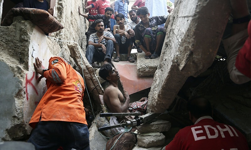 Volunteers try to rescue a trapped resident in Karachi, Tuesday, July 18.— AP