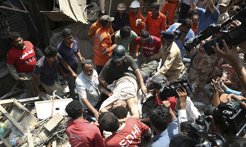 Volunteers carry an injured person rescued from the collapsed apartment.— AP