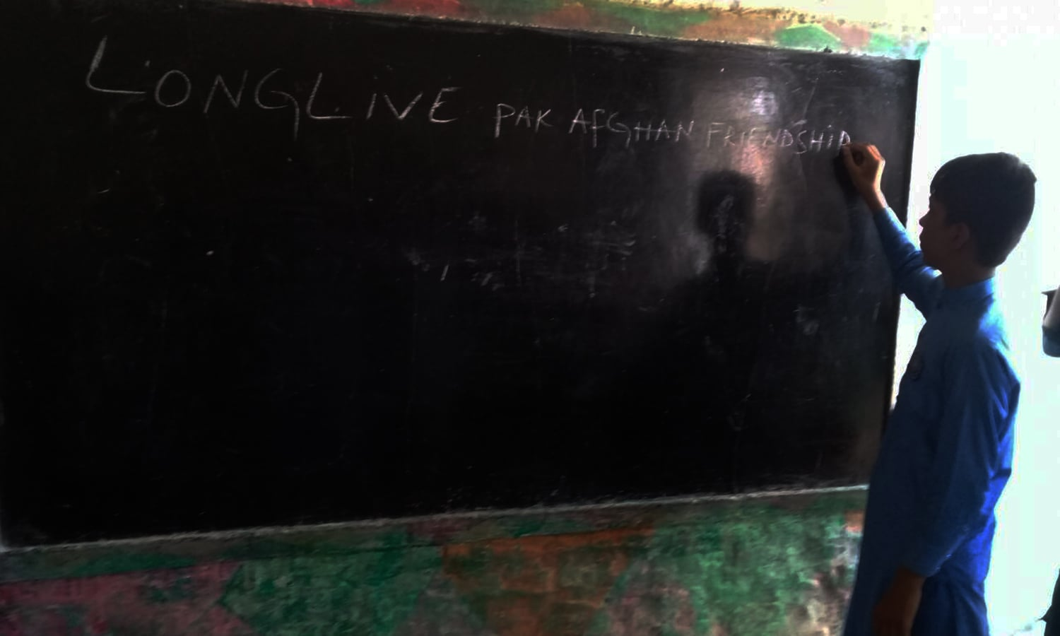 "A boy writes ""Long live Pak Afghan friendship on a blackboard in school. — Photo by author"