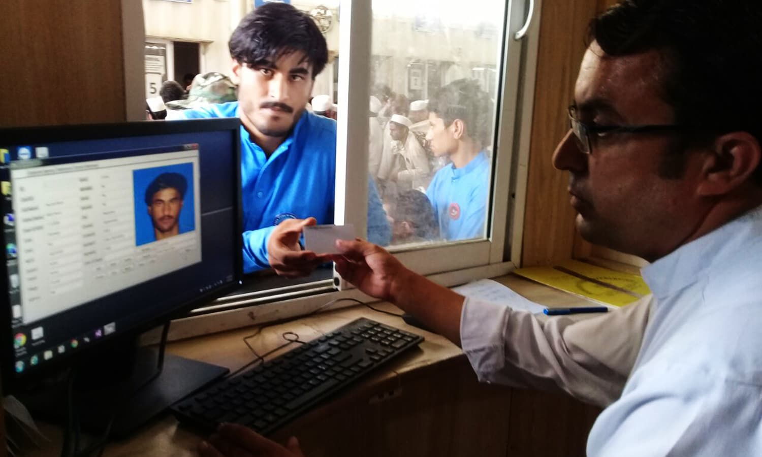 A youngster shows his special ID at a special counter setup at the Torkham border crossing. — Photo by author