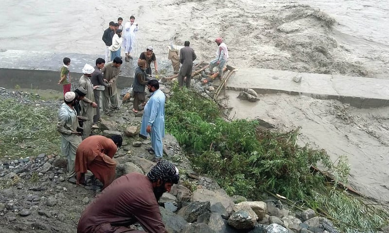The people of Mastuj village striving to contain the flood water from inundating the road. — Dawn