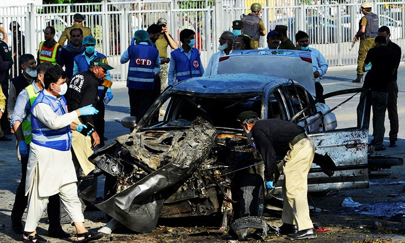 security officials inspect a destroyed vehicle after an explosion in Lahore.—AFP