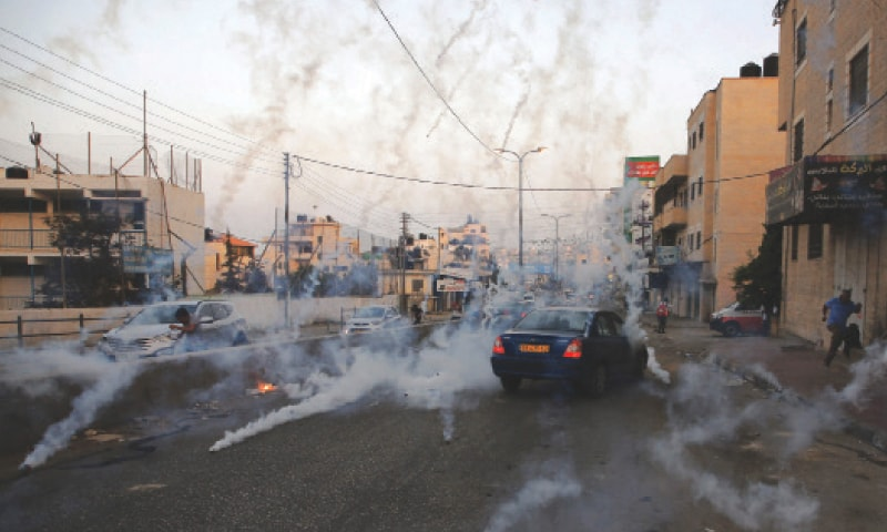 RAMALLAH: Palestinian men run for cover from tear gas during clashes between demonstrators and Israeli forces at the Qalandiya checkpoint, between Ramallah and Jerusalem, on Monday.─AFP