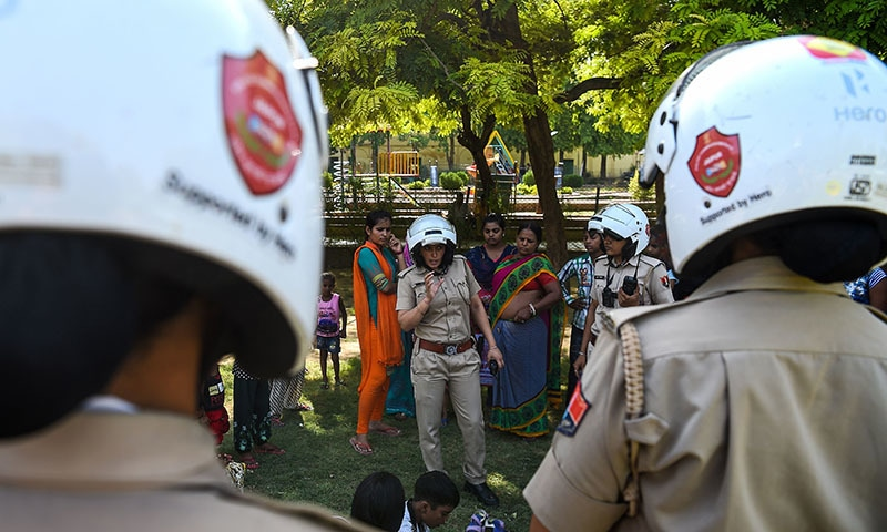 Saroj Chodhuary, an Indian police constable and a member of a newly launched female police unit, explains about the women helpline numbers in a park in Jaipur.─AFP