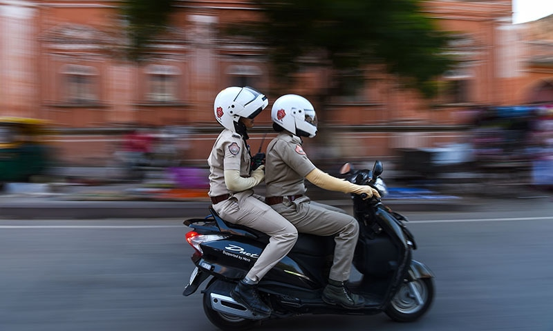 Members of a newly launched female police patrol unit drive through the old city in Jaipur.─AFP