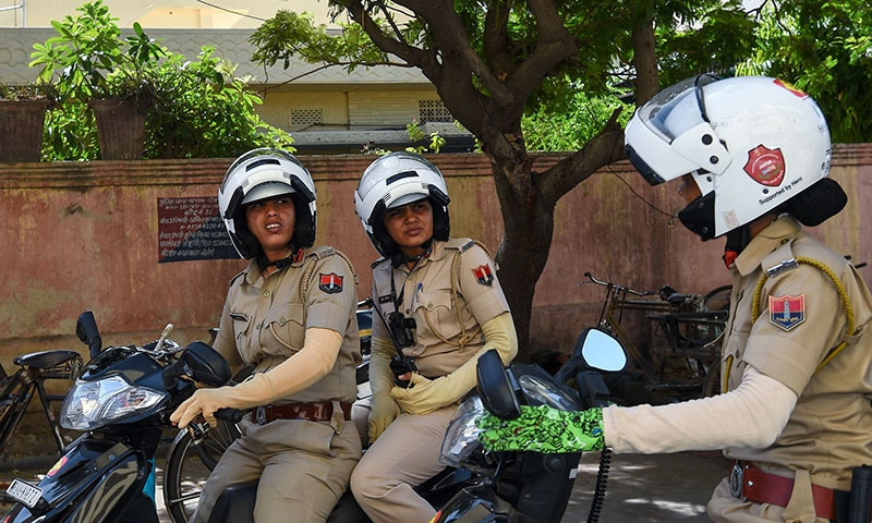 Members of a newly launched female police patrol unit drive through the old city area in Jaipur. ─AFP