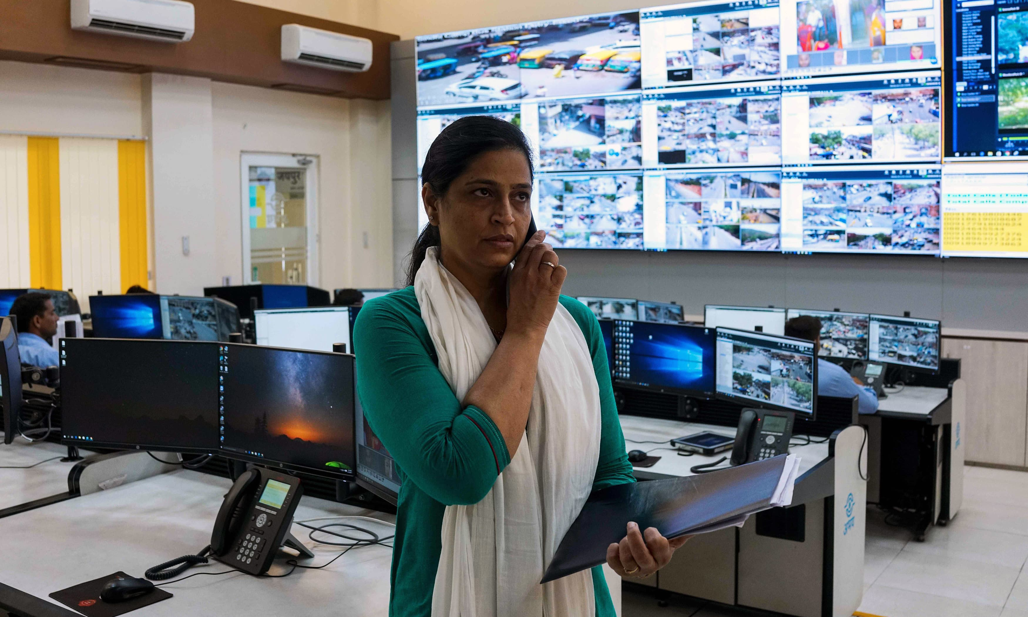 Kamal Shekhawat, head of the female police patrol unit, talks on the phone while standing inside the police command centre at the Jaipur Commissionate Headquarters. — AFP
