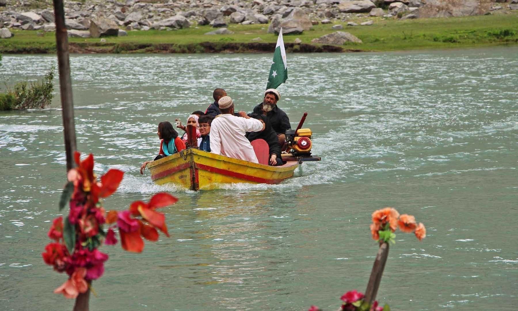 جھیل سیف اللہ میں ایک سیاح خاندان کشتی میں گھوم رہا ہے—تصویر امجد علی سحاب