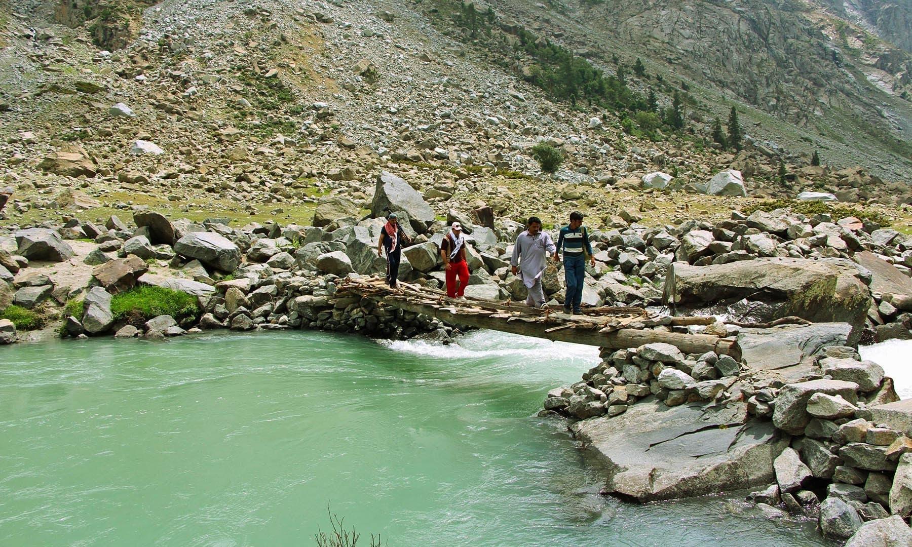 ڈونچار آبشار تک رسائی حاصل کرنے کے لیے لکڑیوں کے اس پل پر سے گزرنا پڑتا ہے—تصویر امجد علی سحاب