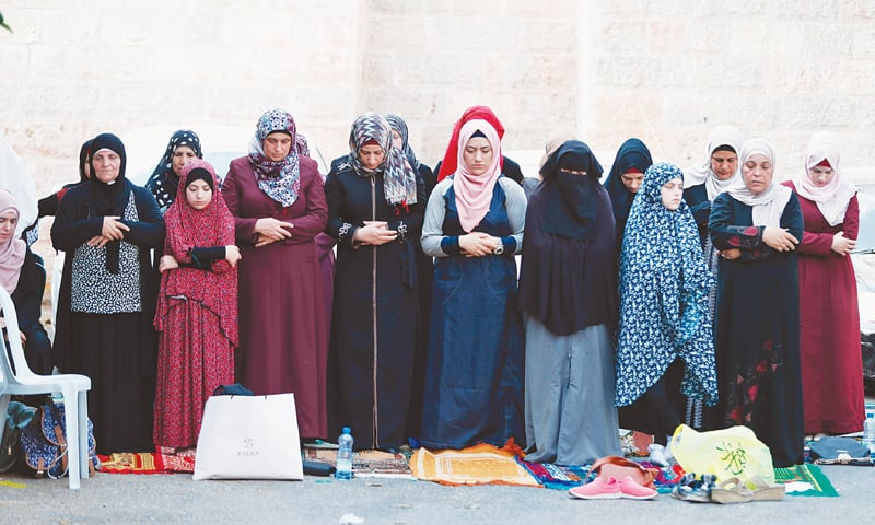 Women pray outside Jerusalem's Old City on Tuesday after Muslim leaders said worshippers should continue to boycott the Al Aqsa mosque compound even though Israelis altered some security measures that had triggered deadly violence.—AFP