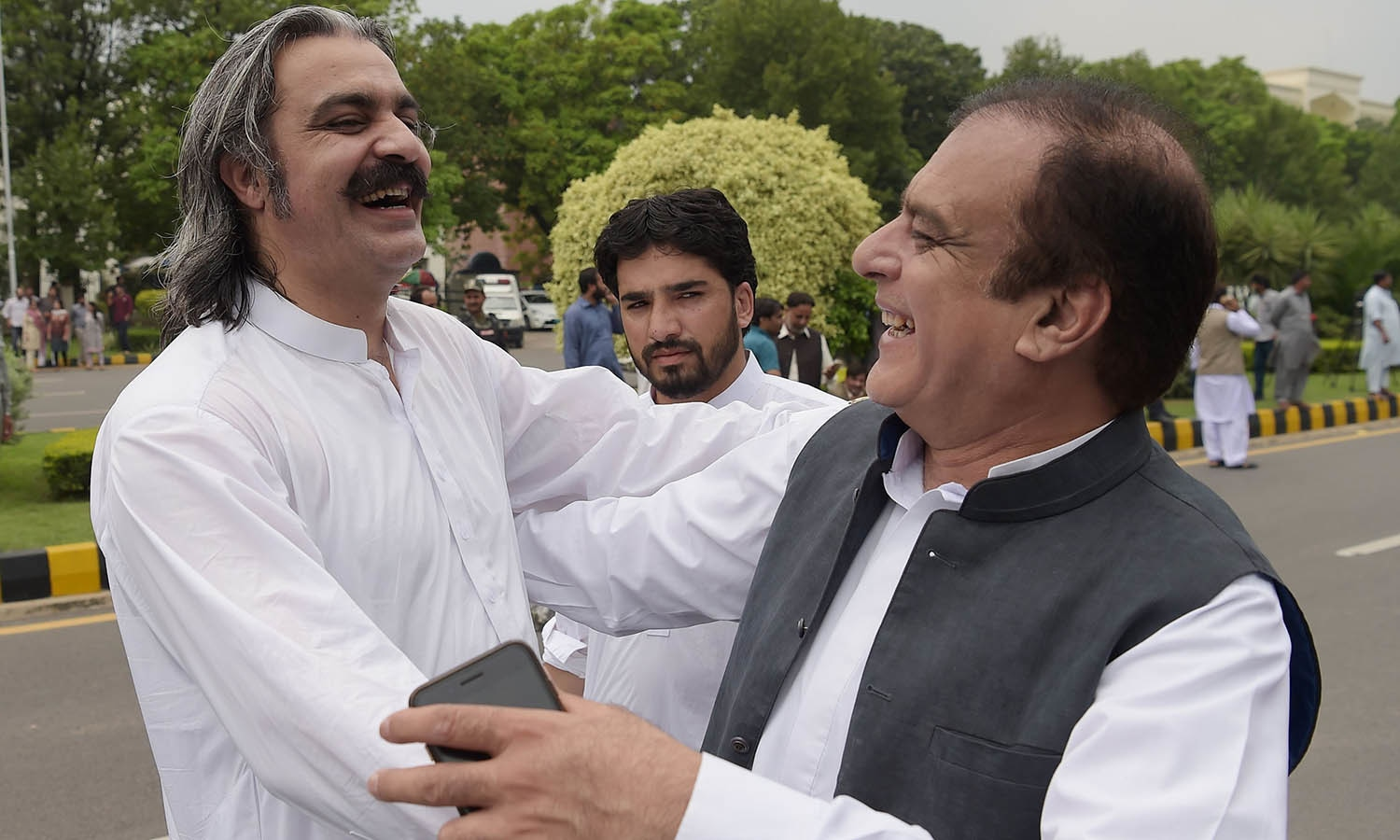 PTI leaders Ali Amin Khan Gandapur and Shibli Faraz celebrate after the SC verdict against Nawaz Sharif. —AFP