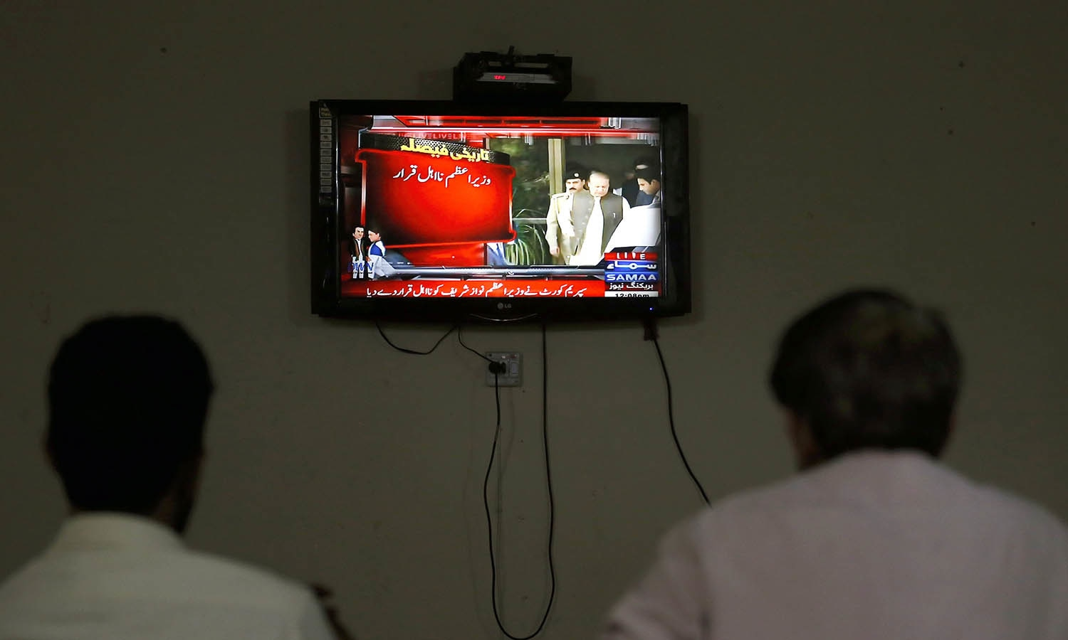 People watch a news channel flashing alerted news regarding Supreme Court decision. —AP