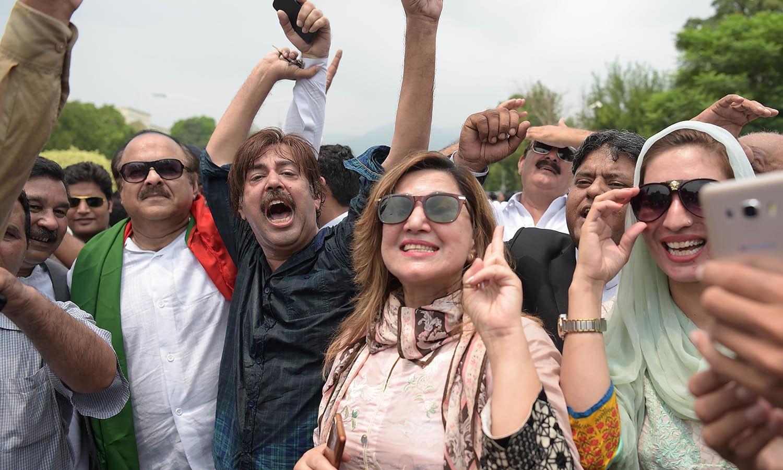 پاکستان تحریک انصاف کے کارکنان نواز شریف کے نااہل ہونے پر خوشی سے نعرے بازی کرتے ہوئے — فوٹو/ اے ایف پی