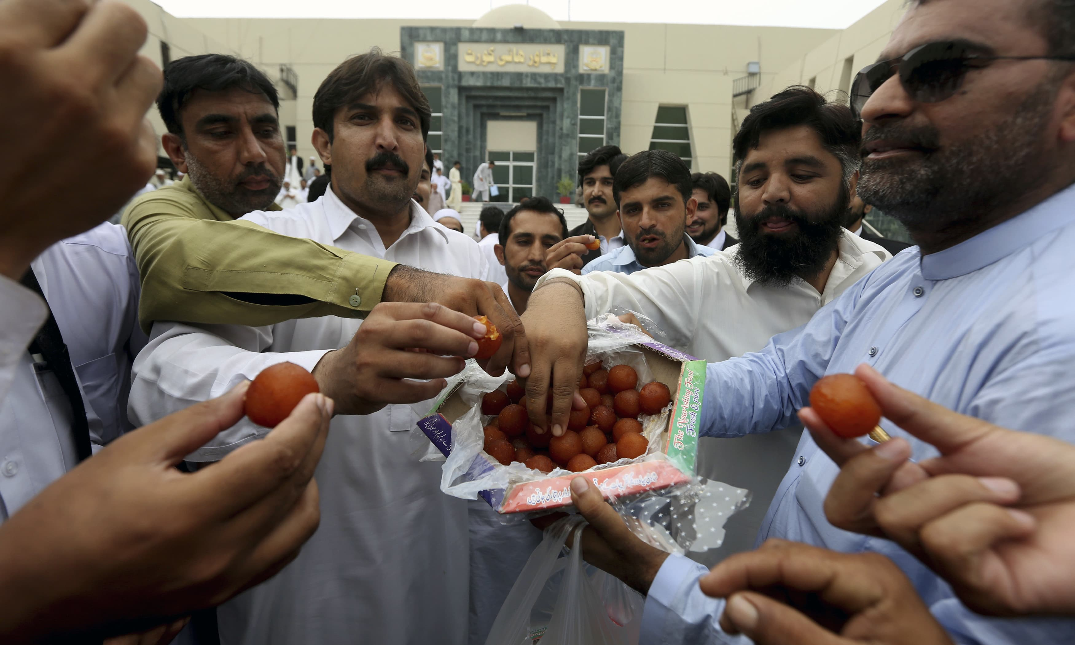 PTI supporters share sweets to celebrate the dismissal Nawaz Sharif. —AP
