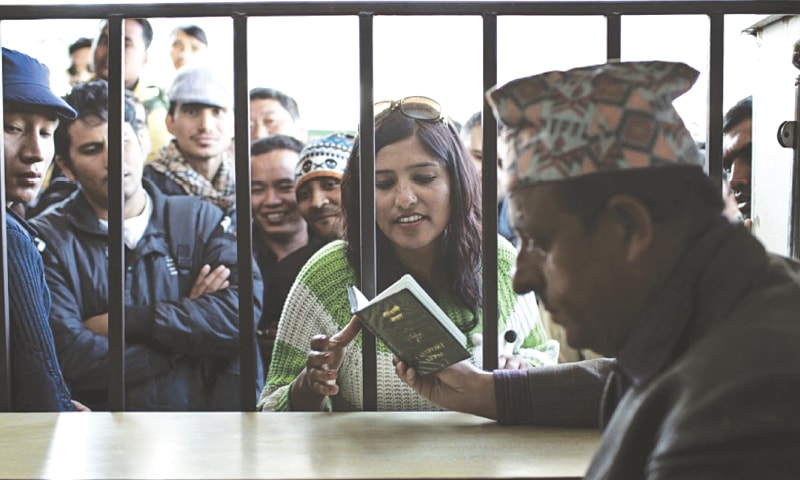 A Nepali migrant worker receives her passport from a government officer in 2013 after obtaining a foreign employment permit at the Department of Foreign Employment in Kathmandu, Nepal | (Narendra Shrestha for The Washington Post)