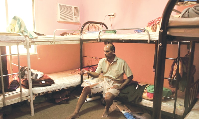 Kuttamon Chembadnan Velayi of Kerala, India, speaks to journalists while sitting on his bed in a room he shares with seven other Indian labourers in Doha, Qatar, in 2015 | (Maya Alleruzzo/Associated Press)