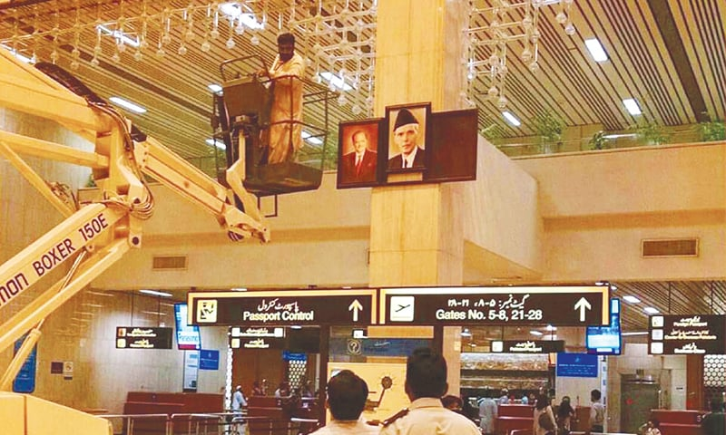 KARACHI: Authorities of the Jinnah International Airport remove former prime minister Nawaz Sharif's photo on Saturday after his disqualification by the Supreme Court in the Panama Papers case.—PPI