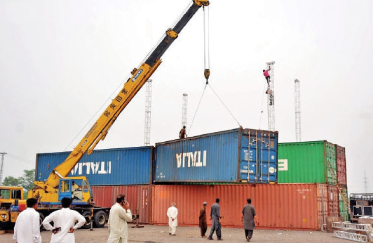Containers being placed to prepare a stage ahead of the PTI public gathering in Islamabad. — INP