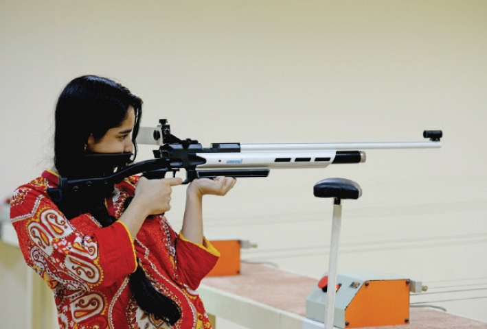 A young woman aims an air rifle at the 10-metre shooting range.