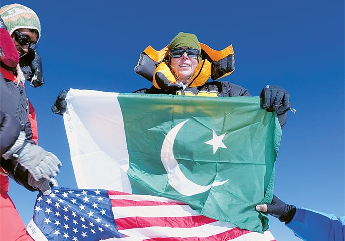 VANESSA O'Brien holds a Pakistan flag while a colleague unfurls the Stars and Stripes at the summit.—Dawn