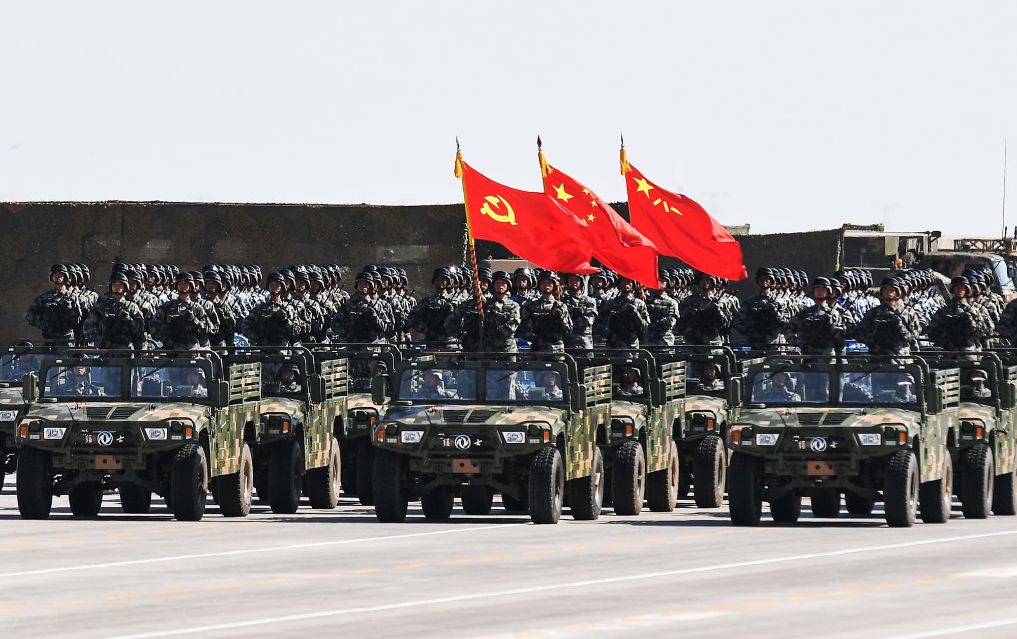 Chinese soldiers carry the flags of (L to R) the Communist Party, the state, and the People's Liberation Army during a military parade at the Zhurihe training base in China's northern Inner Mongolia region on July 30, 2017. ─ AFP