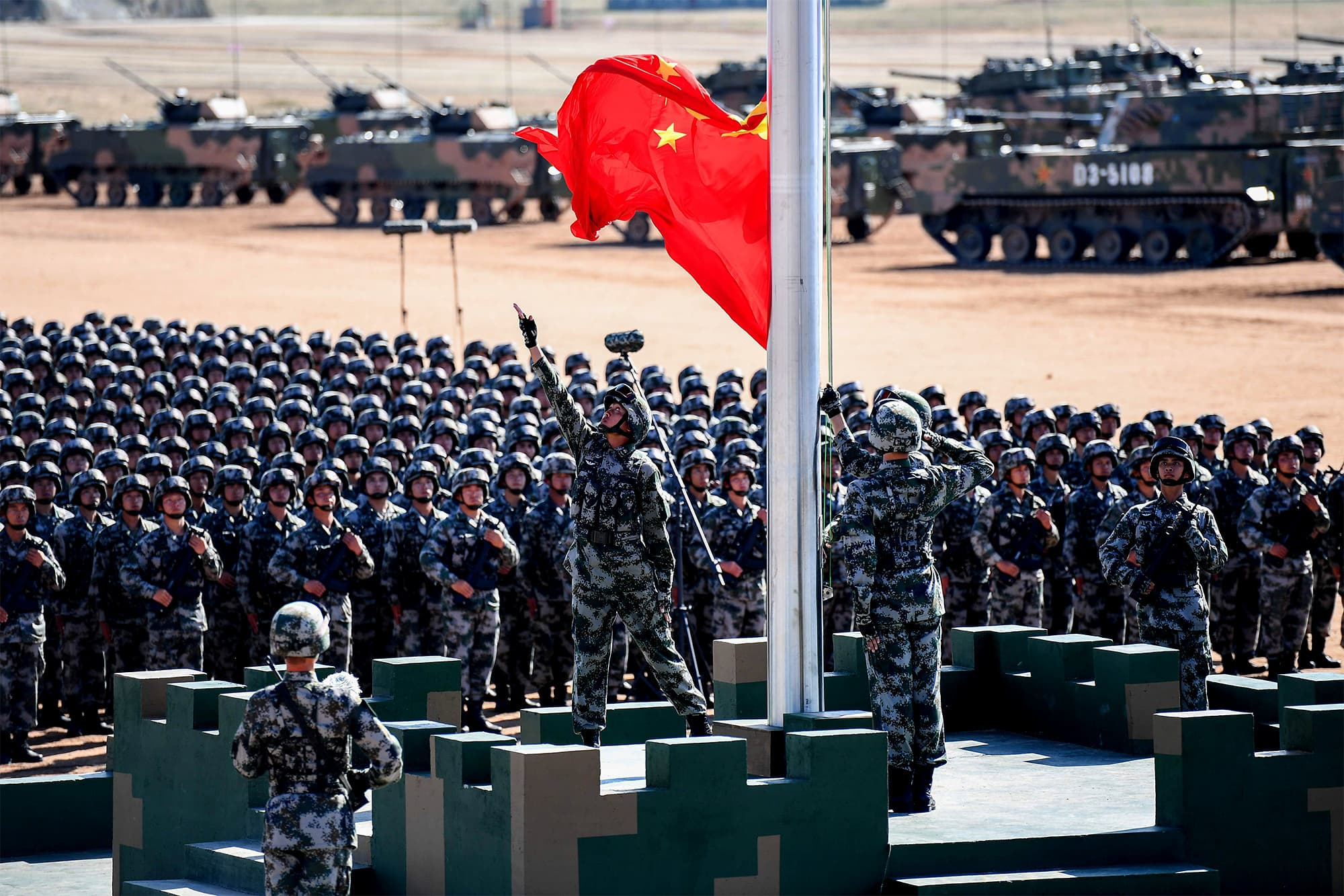 The Chinese flag is raised during a military parade at the Zhurihe training base in China's northern Inner Mongolia region on July 30, 2017. ─ AFP