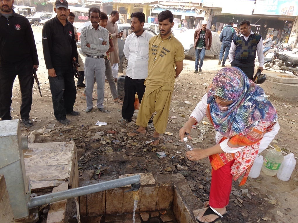 Taking a water sample from community hand pump in Karachi (image courtesy: PCRWR)