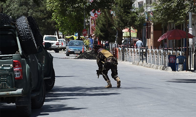 A member of the Afghan security forces walks on the street at the site of a blast near Iraq's embassy in Kabul. ─ AFP