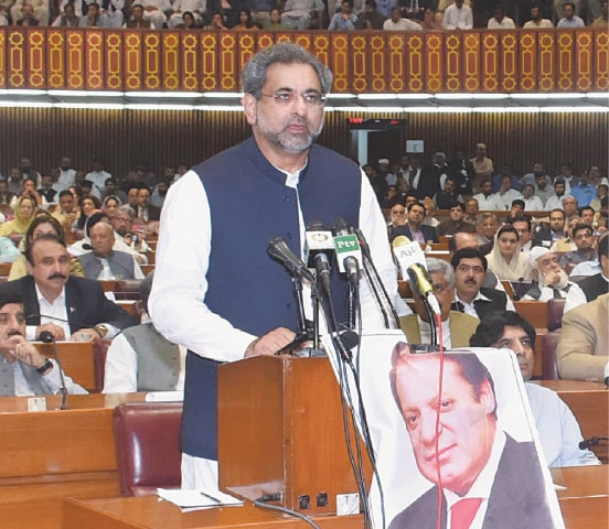 NEWLY-ELECTED Prime Minister Shahid Khaqan Abbasi speaks in the National Assembly on Tuesday. A portrait of ousted PM Nawaz Sharif was strategically placed on Mr Abbasi's desk by his supporters.—AFP