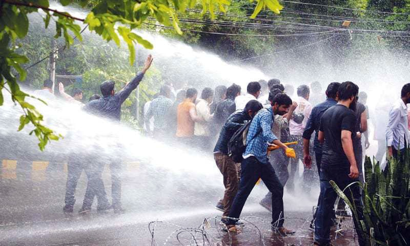 LAHORE: Police officials use a water cannon in an effort to stop protesting doctors from entering the red zone on Tuesday.— PPI