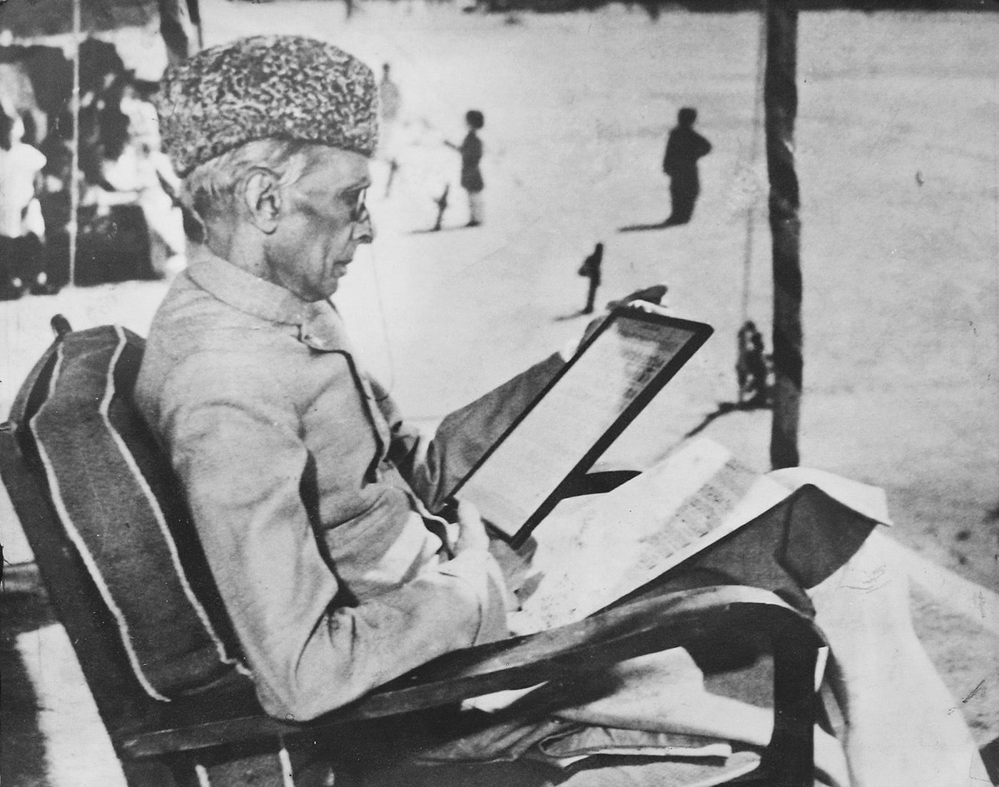 Quaid-i-Azam Mohammad Ali Jinnah turns his attention to an early musical score of Pakistan's national anthem after inspecting an anti-aircraft regiment in Malir on February 21, 1948. — Courtesy Lahore Museum Archives