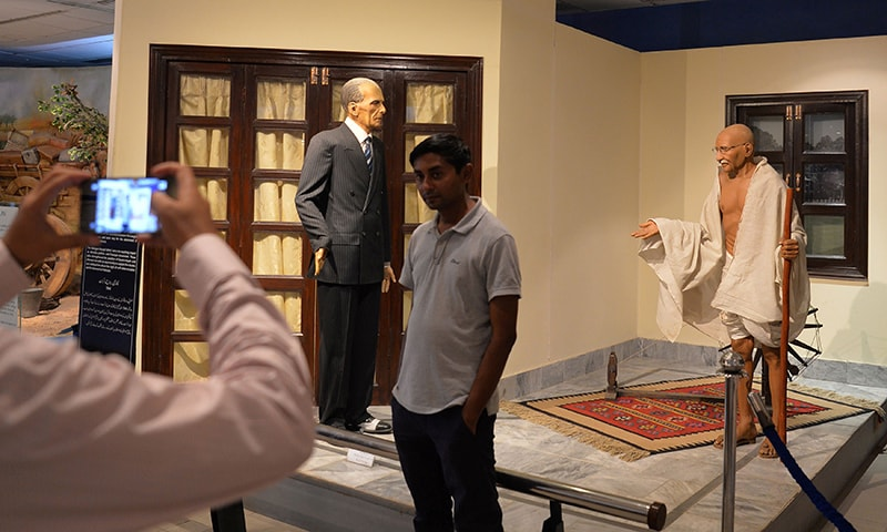 A visitor takes a photo with figures of Quaid-i-Azam Muhammad Ali Jinnah and Indian independence icon Mahatma Gandhi (R) at the Pakistan Monument Museum in Islamabad.— AFP