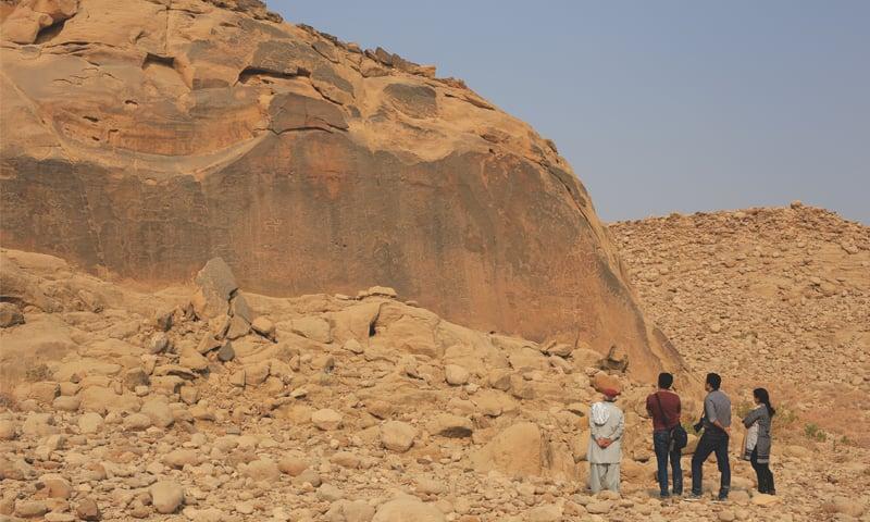 Left to right: the guide, Mohsin Soomro, Zaman Narejo and Sara Rashid view the public canvas of Malango Jabal