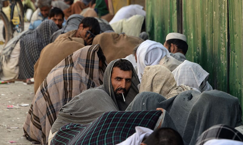 Afghan drug addicts seen smoking heroin on a street in Jalalabad.─AFP