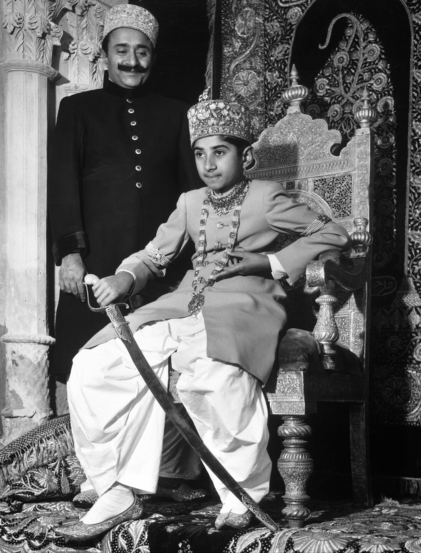 "Mir George Ali Murad Khan Talpur II – ""the boy prince of Khairpur"" – at Faiz Mahal, Khairpur, in December 1947. He is seated on his throne holding a sword, while his Regent, Mir Ghulam Hussain Khan Talpur, looks on.— Courtesy Mir of Khairpur Family Archive"