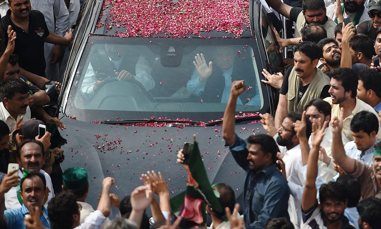 نواز شریف گاڑی سے ہاتھ ہلا کر مسلم لیگ کے کارکنوں کے نعروں کا جواب دے رہے ہیں — فوٹو: اے ایف پی
