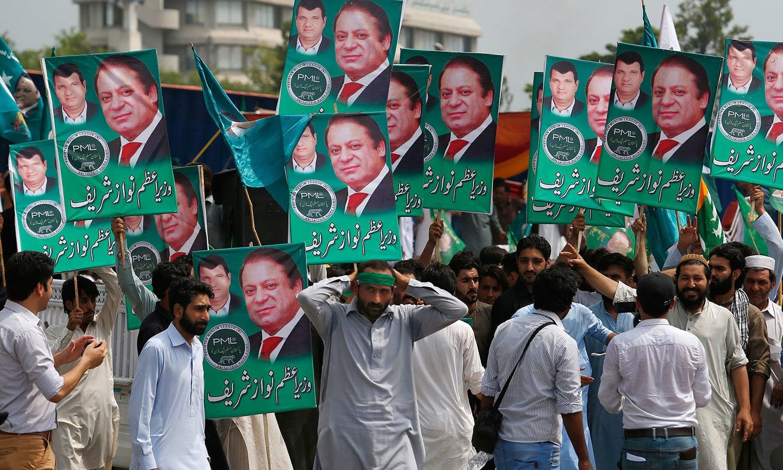 اسلام آباد سے لاہور جانے والے لیگی کارکنوں نے نواز شریف اور امیر مقام کے مشترکہ بنائے گئے بینرز اٹھا رکھے ہیں — فوٹو: اے پی