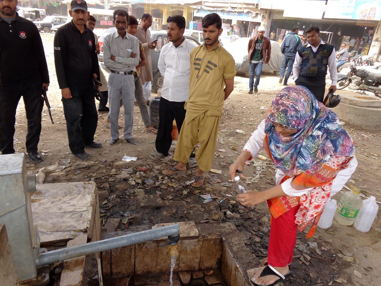 کراچی کے ایک ہینڈ پمپ سے پانی کے نمونے اکھٹے کیے جا رہے ہیں۔ فوٹو PCRWR