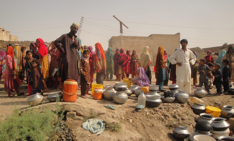 سندھ کے ضلع جامشورو کے گاؤں نگر خان بروہی منچھر کی خواتین پانی کے انتظار میں کھڑی ہیں۔ فوٹو PCRWR
