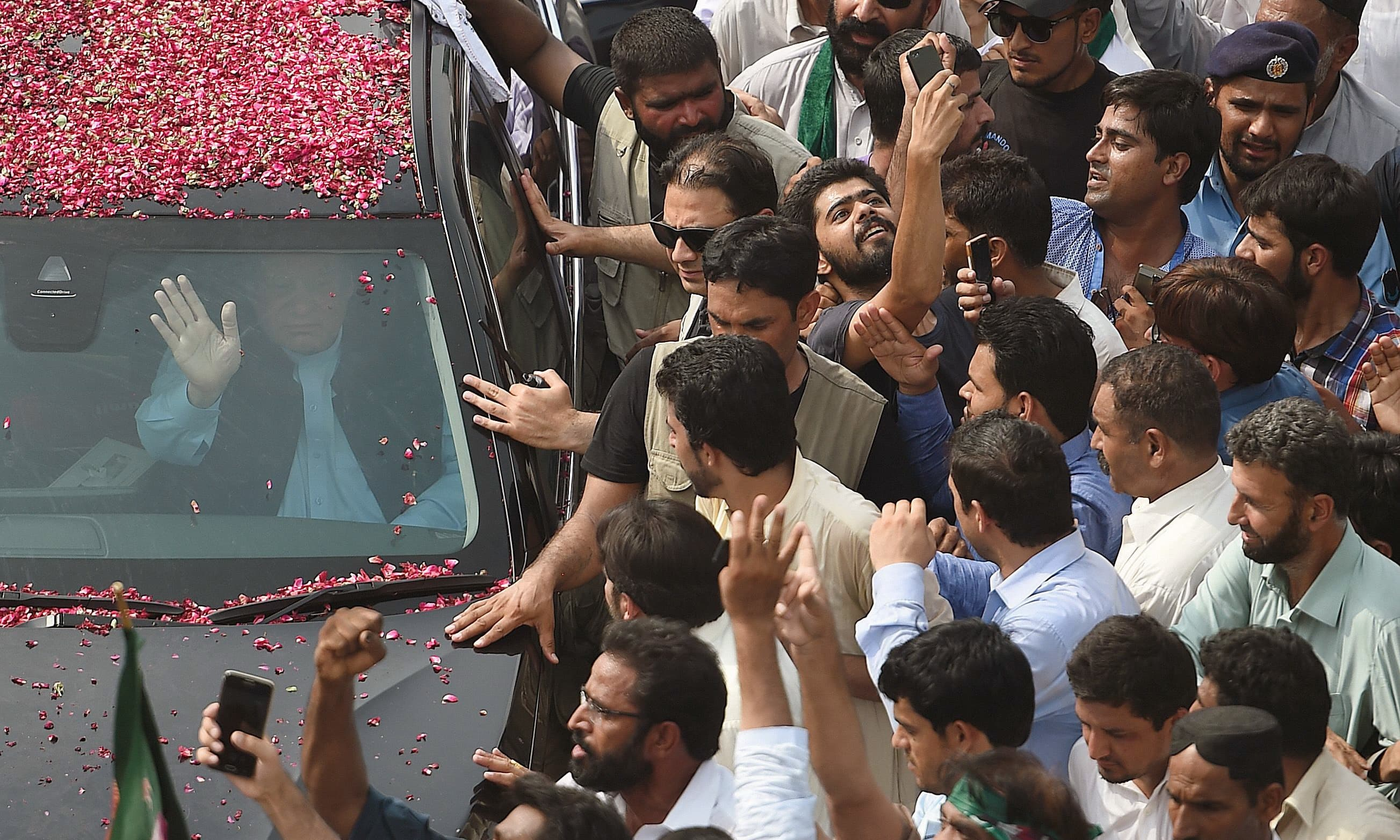 Nawaz Sharif waves to supporters from his car as he begins a rally from Islamabad to Lahore. —AFP