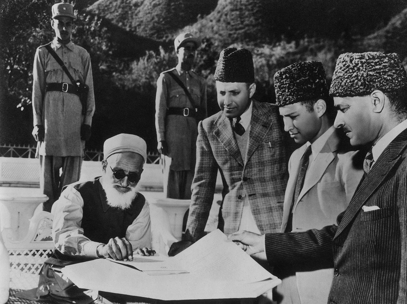 Miangul Abdul Wadud signs the Instrument of Accession enabling Swat to join Pakistan in 1947. On the right are his son Miangul Abdul Haq Jahanzeb, his grandson Miangul Aurangzeb and the Chief Secretary of Swat, Mr Attaullah. — Courtesy Miangul Aurangzeb Archives, Swat
