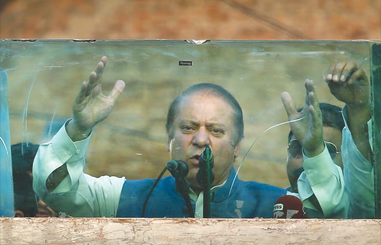 JHELUM: Ousted prime minister Nawaz Sharif addresses the crowd from a makeshift stage behind bulletproof glass on Thursday.—AP