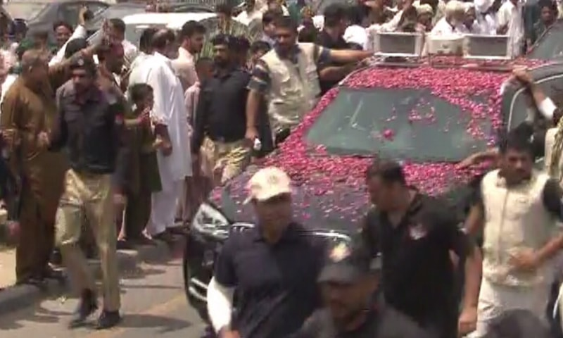 Sharif's convoy was showered with rose petals as it crossed Sarae Alamgir on its way to Kharian. ─ DawnNews